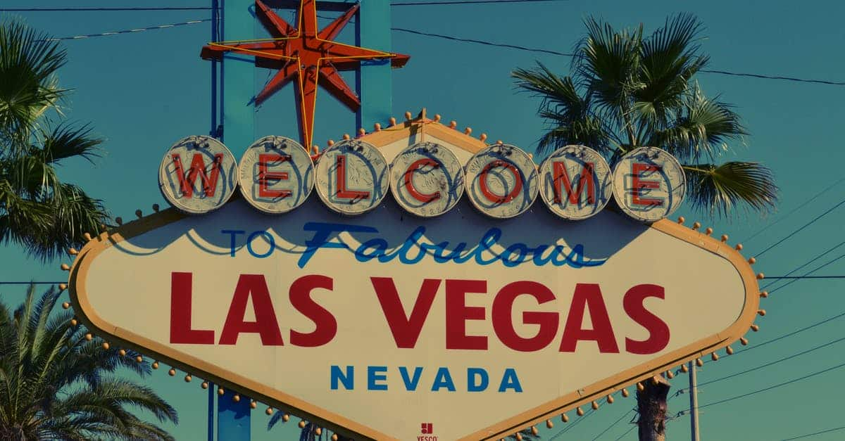A sign in front of a palm tree with Welcome to Fabulous Las Vegas sign in the background